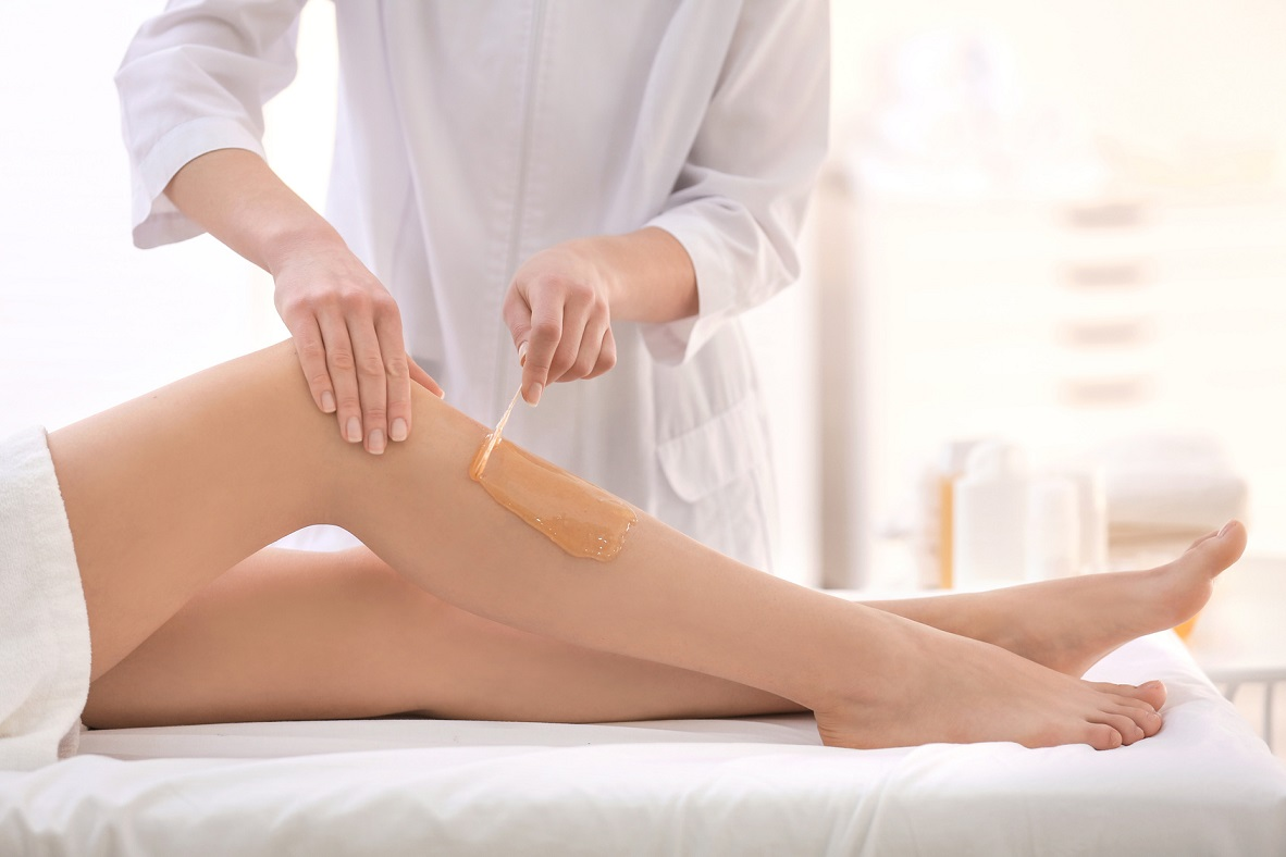 Beautician waxing female legs